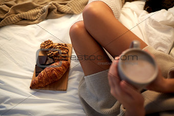 close up of woman with sweets and drink in bed