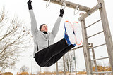 young man exercising on horizontal bar in winter