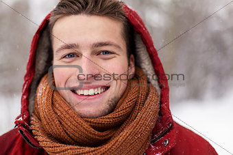close up of happy man in winter jacket with hood