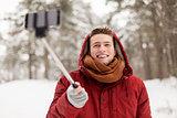 happy man taking selfie by smartphone in winter
