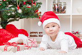Cute baby in a Santa hat next to Christmas tree with presents