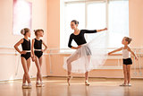 Young girl warming up and talking to younger classmates at ballet dancing class