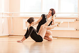 Ballet teacher showing young girl how to perform exercise on floor