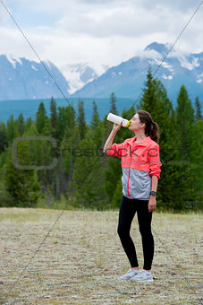 Beautiful woman runner drinking water outdoors. Mountains background.