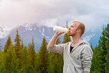 Men runner drinking water outdoors. Mountains background.