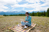 Beautiful girl in a field on mountains, using  tablet pc.