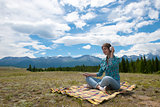 Woman in headphones listening music in a field and at the mountain.