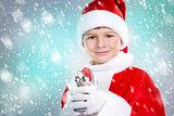 boy dressed up as Santa in winter setting