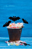 Halloween candy bucket, paper bats and rubber spider on blue woo
