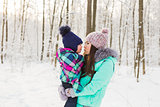 Young brunette mother with her daughter outdoors. Winter time