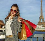 happy elegant woman with shopping bags near Eiffel tower, Paris