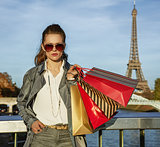 trendy woman in trench coat with shopping bags in Paris, France