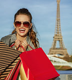 cheerful elegant woman with shopping bags near Eiffel tower