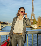 smiling young elegant woman using smartphone in Paris, France