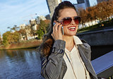 smiling fashion-monger talking on smartphone near Eiffel tower