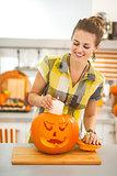 housewife putting candle inside orange pumpkin Jack-O-Lantern