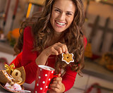 Happy young woman in red dress having snack in christmas decorat