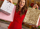 Happy young woman showing shopping bags in christmas decorated k