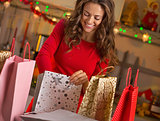 Smiling young woman with shopping bags in christmas decorated ki