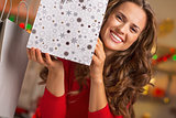 Smiling young woman showing christmas shopping bag