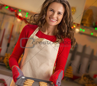 Portrait of young housewife with pan of fresh cookies in christm