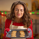 Young housewife enjoying pan of fresh cookies