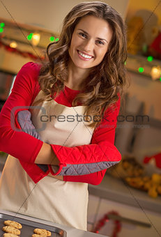 Portrait of happy young housewife with pan of fresh cookies in c