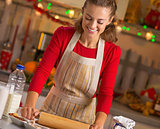 Happy young housewife rolling pin dough in christmas decorated k