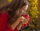 Woman having cup of hot chocolate and cookie near Christmas tree
