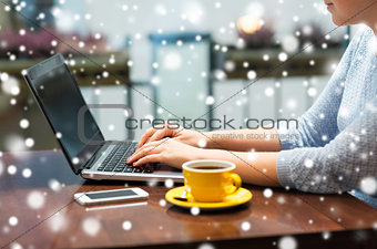 close up of woman typing on laptop with coffee
