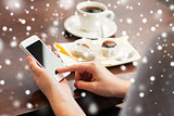 woman with smartphone, coffee and dessert