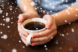 close up of woman holding hot black coffee cup