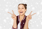 happy smiling teenage girl showing peace sign