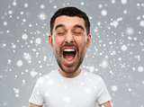 crazy shouting man in t-shirt over snow background