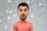 surprised man in polo t-shirt over snow background