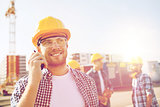 group of smiling builders in hardhats with radio
