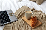 laptop, coffee and croissant on bed at cozy home