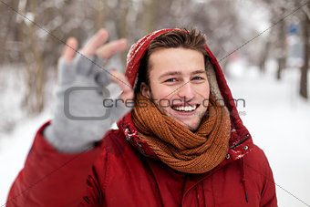 happy man in winter jacket showing ok hand sign