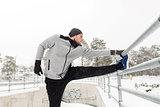 sports man stretching leg at fence in winter