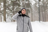 sports man with earphones in winter forest