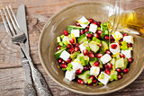 Fresh  green salad with pomegranate seeds, cucumber and feta che