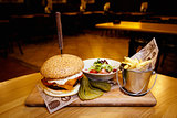 Tasty Steak Burger with Ham Slices on a Wooden Bar fries and vegetables