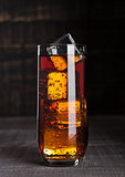 Glass of cola soda with ice cubes on wooden board