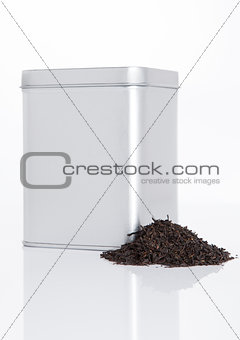Black tea steel jar with loose tea next to it