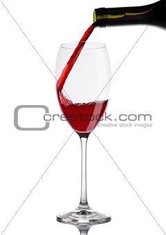 Pouring red wine from bottle to glass on white