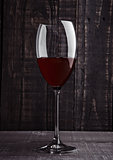 Glass of red wine with reflections on wooden board
