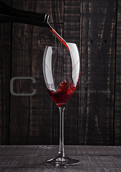 Pouring red wine into the glass from bottle