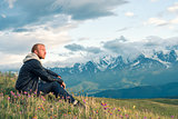 Traveler sitting on top of a mountain and looks into the distance. Mountains.