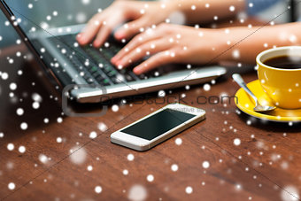 close up of smartphone and hands typing on laptop