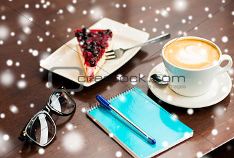 close up of notebook with pen, coffee cup and cake
